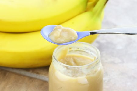 Pureed baby food from a jar with fresh bananas in background. photo