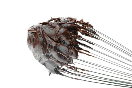 A whisk with chocolate frosting isolated on a white background.