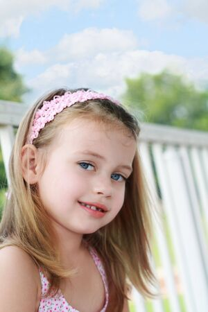 Portrait of a little girl sitting on a porch swings on a beautiful summer day.