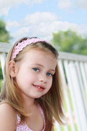 Portret van een klein meisje, zittend op een portiek schommeling op een mooie zomer dag.  Stockfoto