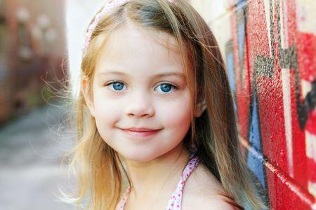 bionda occhi azzurri: Bambina in un contesto urbano in sorrisi alla fotocamera.