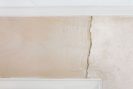 door casing: Interior wall with glazed paint shows structural damage from poor foundation. Crack extends from ceiling to windowdoor frame.