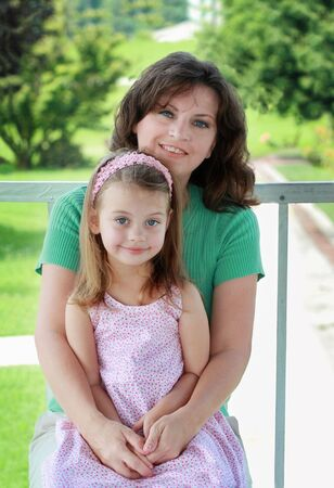 to lap: Portrait of a mother in her 40s with her young daughter. Stock Photo