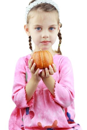 Beautiful little girl holds a pumpkin up to the viewer. photo
