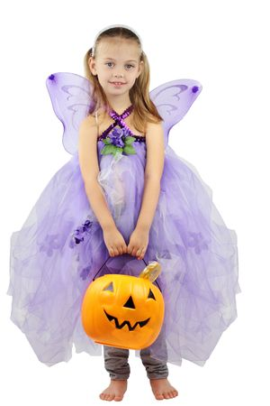 Child dressed as a fairy for Halloween and holding a basket of candy. photo