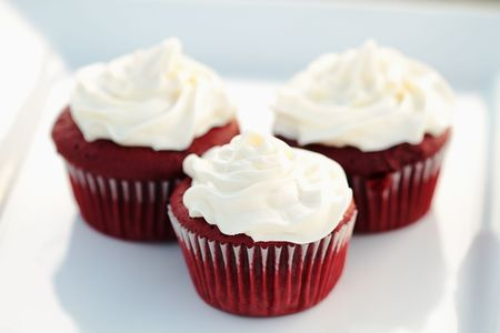 Three red velvet cupcakes on a white dish with extreme shallow DOF.
