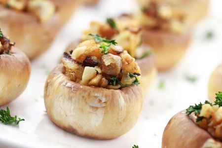 Stuffed mushrooms filled with bread crumbs, cheese, mushroom stems, fresh  parsley,onions and Macadamia nuts. Extreme shallow DOF with selective focus on center mushroom.
