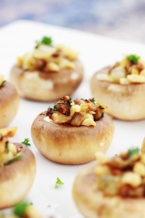 Gevulde champignons opgevuld met broodkruimels, kaas, mushroom stengels, verse peterselie, uien en Macadamia noten. Extreme ondiepe DOF met selectieve aandacht op center paddestoel. Stockfoto