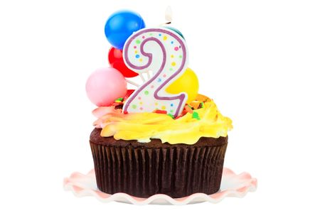 Chocolate birthday cake with number  two candle and plastic balloons. Isolated on a white background. Imagens