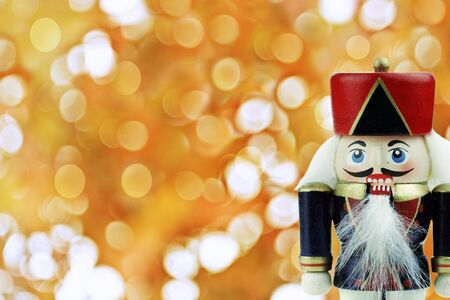 Wooden Nutcracker against a background of golden holiday lights .