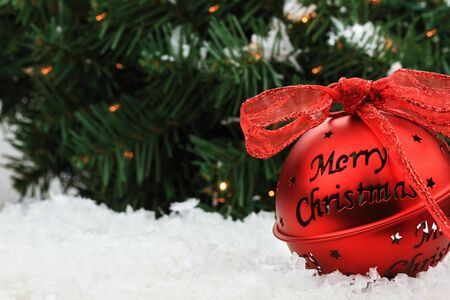 Beautiful red Christmas bell ornament lies in the snow with copyspace and a message of &quot,Merry Christmas.&quot, Stock Photo