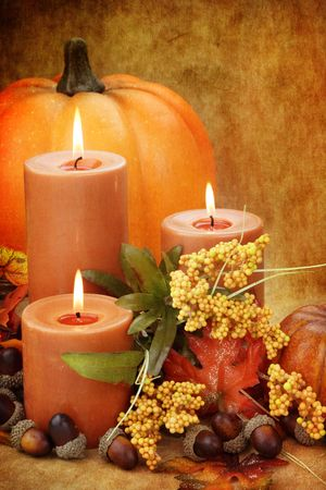 grunged: autumn still life of burning candles surrounded by colorful leaves, pumpkins and acorns.