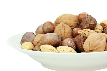 A variety of whole mixed nuts in the shell against a white background.  photo