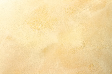 Macro of stucco wall with soft warm tones.
