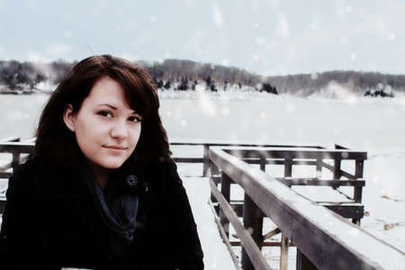 Young woman stands near a frozen lake. photo