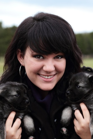 Attractive young woman holds two adorable purebred Norweigan Elkhound puppies. photo