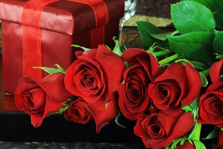 Upclose image of beautiful long stem red roses with gift in a breakfast tray on a bed. photo