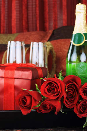 Beautiful long stem red roses with gift, wine and glasses in a breakfast tray on a bed. photo