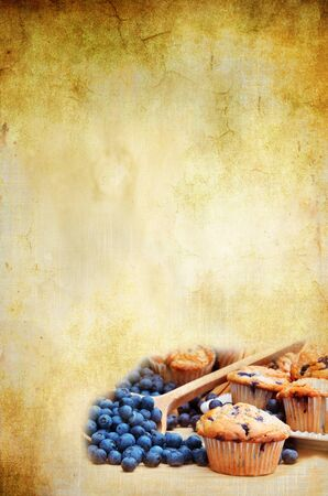 Blank background for recipe with room for copyspace. Blueberry muffins with fresh blueberries spilling from a wooden spoon in lower corner.