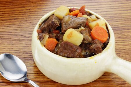 Delicious beef stew served in an onion soup crock with spoon.