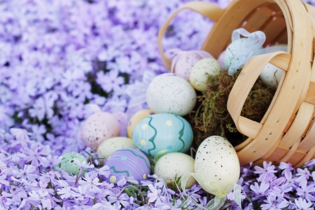 Easter eggs spilling from a basket into a bed of spring flowers. Selective focus on lower portion of image with extreme shallow DOF. photo