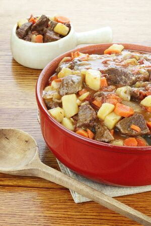 Crock pot full of fresh made roast beef with large chunks of beef, potatoes and carrots. photo