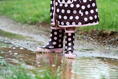 botas de lluvia: Pies de niños jugando en un charco de lodo.   Foto de archivo