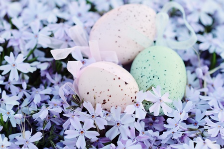 Easter eggs hidden in a bed of spring flowers. Selective focus with extreme shallow DOF. Stock Photo - 8555424