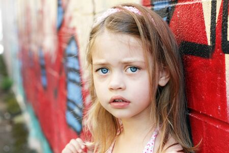 fear child: Worried little girl in an urban setting looking into the camera. Stock Photo