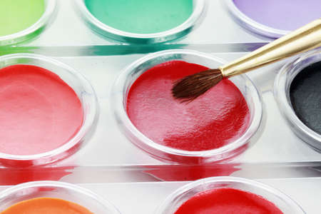 Abstract of new unused palette of childrens multicolor watercolor paints with paint brush.    photo