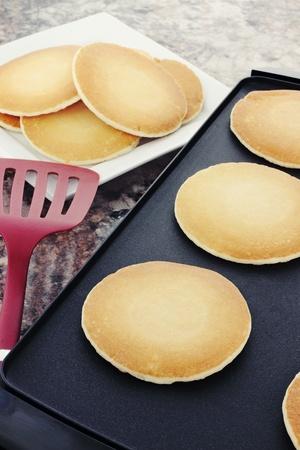hot cakes: Preparando pancakes frescas sobre una plancha de no palo.