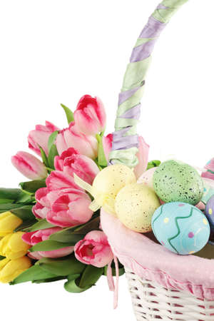 Easter basket and eggs near a bouquet of tulips over a white background. Shallow DOF. Stock Photo - 8660085