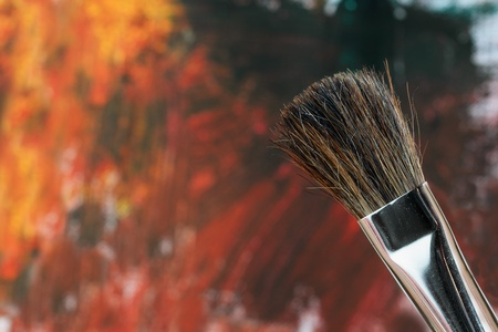 Paintbrush against an abstract grunge painting.