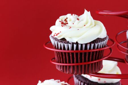 Red velvet cupcake in a red cupcake holder against a red background with copy space included. photo