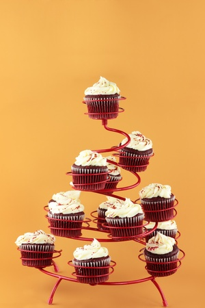 Red velvet cupcakes in a red cupcake holder against a yellowish orange background with copy space included. photo