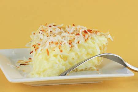 plato del buen comer: Rebanada de pastel de crema de coco casera contra un fondo amarillo. Foto de archivo