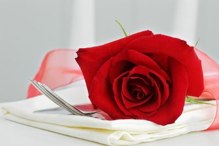Close up of a beautiful red rose with dinnerware. Selective focus with some blur on lower portion of image.