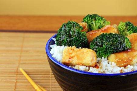 Vegetarian Stir Fry dish of crispy tofu, broccoli and orange sauce with chopsticks. Shallow DOF.