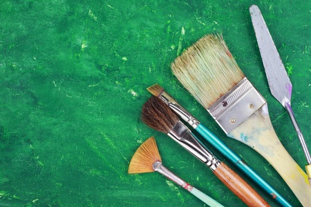 Artist paintbrushes and palette knife against an abstract grunge painting. Stock Photo - 9058003