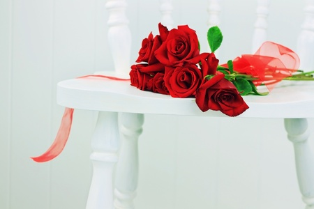 ribbin: Beautiful long stem roses with ribbin on a white chair against a white wall.