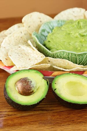 guacamole: Fresh  avocado with guacamole and tortilla chips in the background. Extreme shallow DOF. Stock Photo