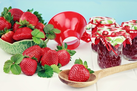 Fresh strawberries and preserves with canning funnel. Shallow DOF. photo