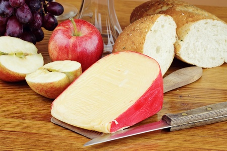 dutch: Dutch Edam cheese with fresh fruit and a loaf of bread. Stock Photo