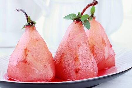 A group of three pears that have been poached in red wine sauce.   photo