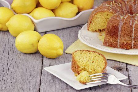 plato del buen comer: Sector de lim�n h�medo bundt pastel con limones reales en segundo plano. Profundidad superficial de campo.