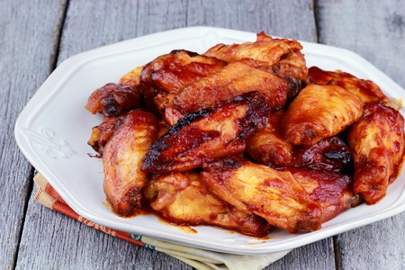 Plate of delicious barbecue chicken wings with shallow depth of field on a rustic background.