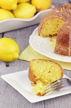 Slice of moist lemon bundt cake with real lemons in background. Shallow depth of field.