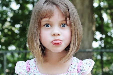 naughty girl: Child sticking out her tongue.  Stock Photo