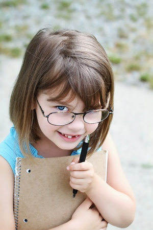 Little girl wearing glasses with pen and book. Shallow depth of field with selective focus on child's face. Stock Photo - 9796530