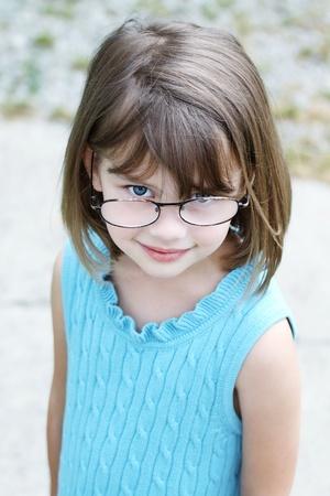어린 소녀 야외에서 안경을 착용 하 고 카메라에 올려.